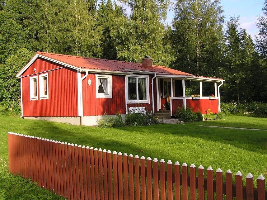 Semesterboende i röd stuga vid skogen