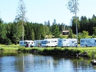 Campingplats med husbilar vid sjön.